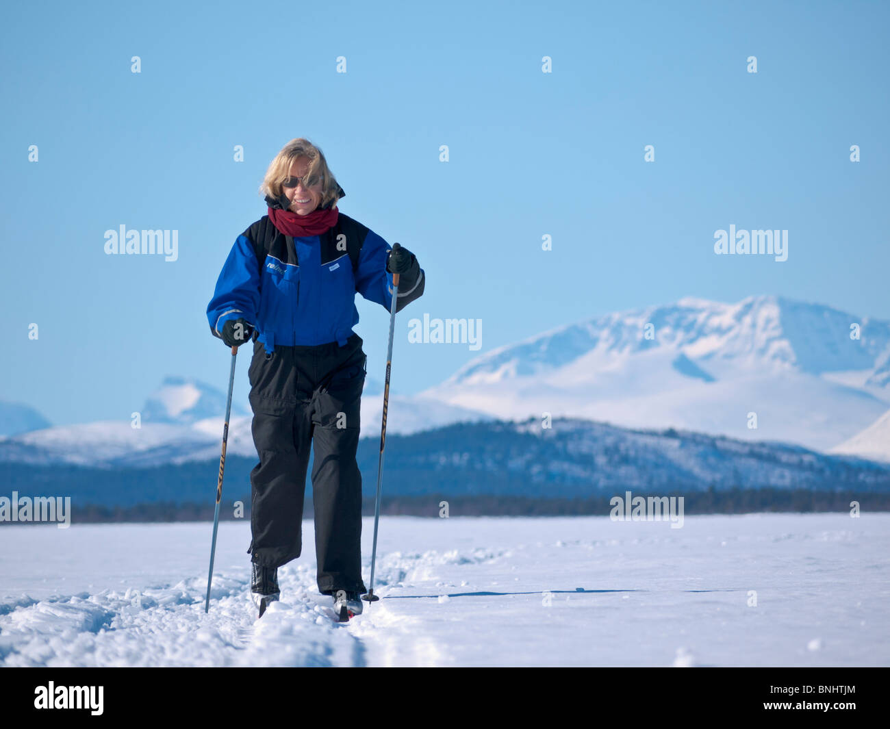 A skiing woman in her fourties makes her way above the frozen Kaalasjärvi lake in front of the Kebnekaise massif - Stock Image