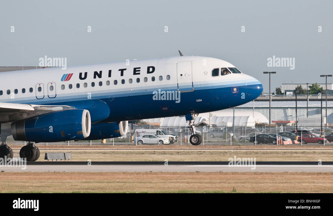 A United Airlines Airbus A320 commercial jet airliner landing at Vancouver International Airport. - Stock Image
