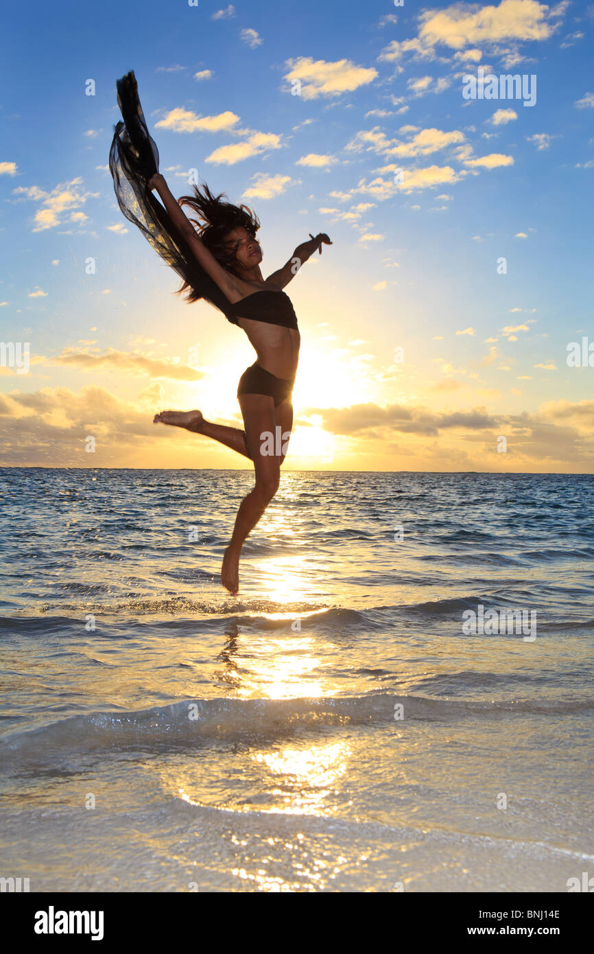 beautiful black female dancer leaping in the air over the ocean at sunrise in the tropics - Stock Image