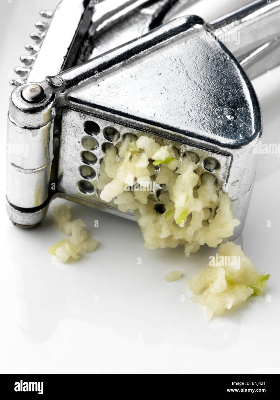 Metal garlic press squeezing - Stock Image