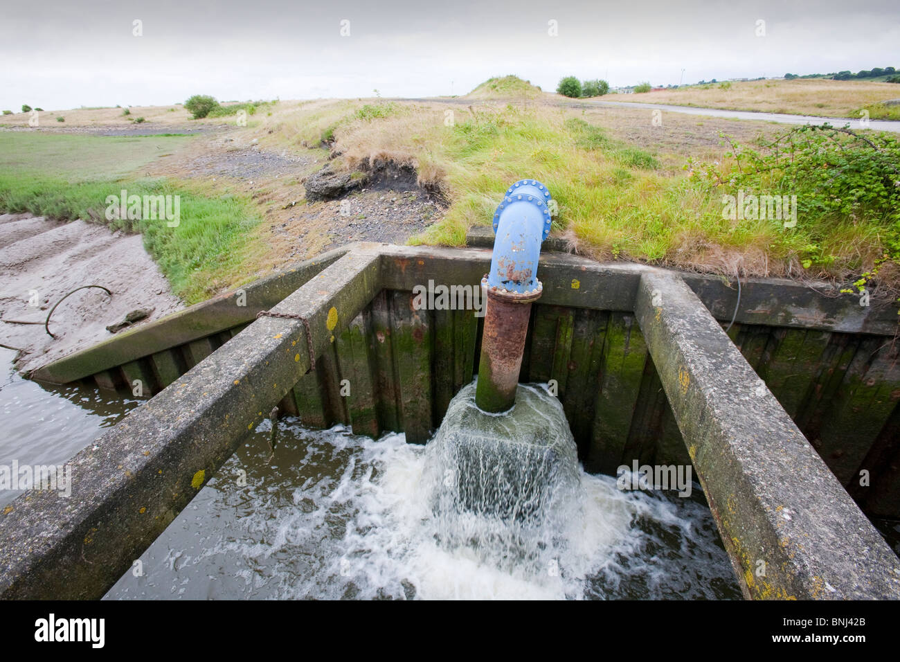 Pumping water off reclaimed salt marsh land, low lying and vulnerable to coastal flooding in North Wales - Stock Image