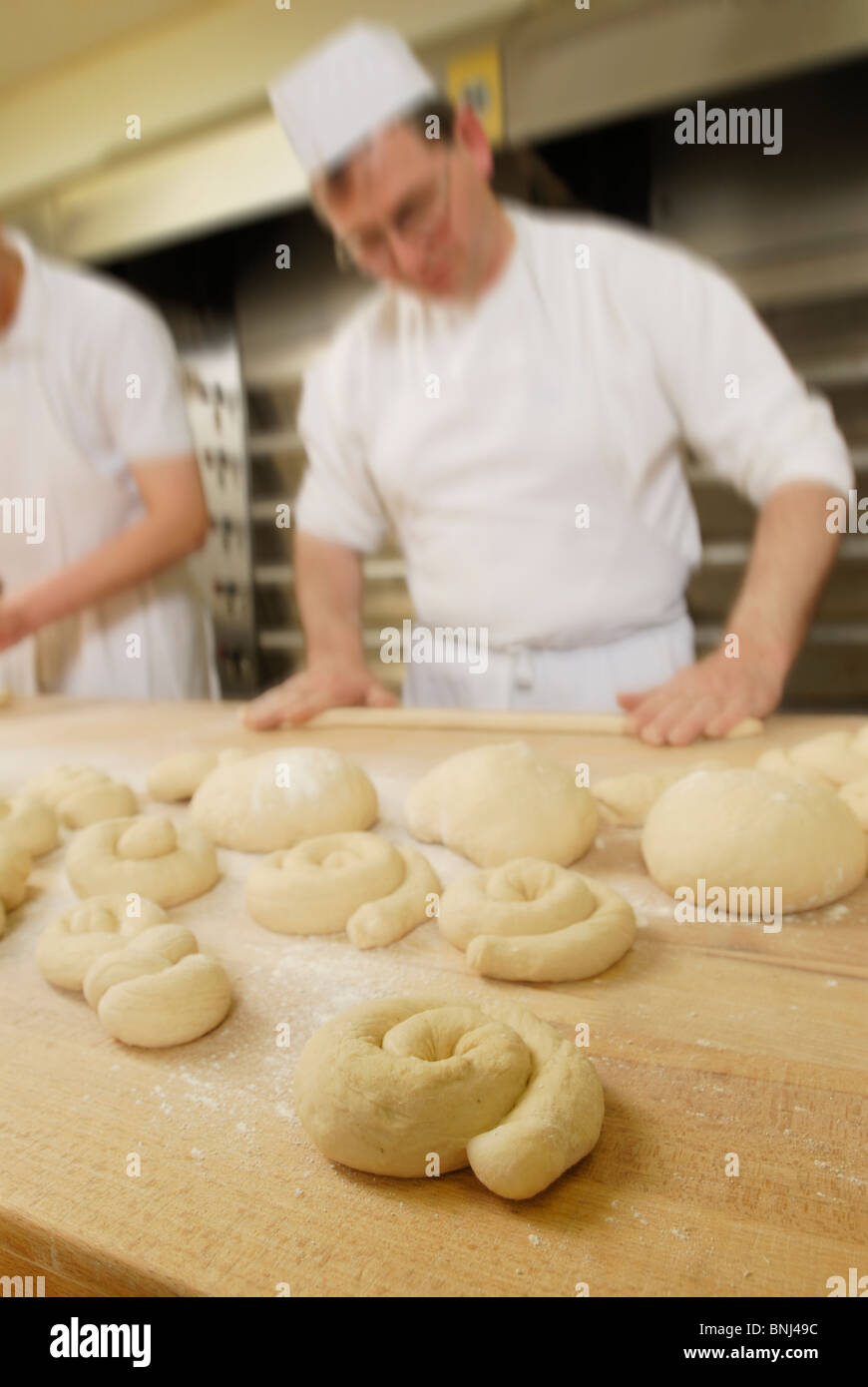 baker, blurred,  forming cakes out of pastry - Stock Image