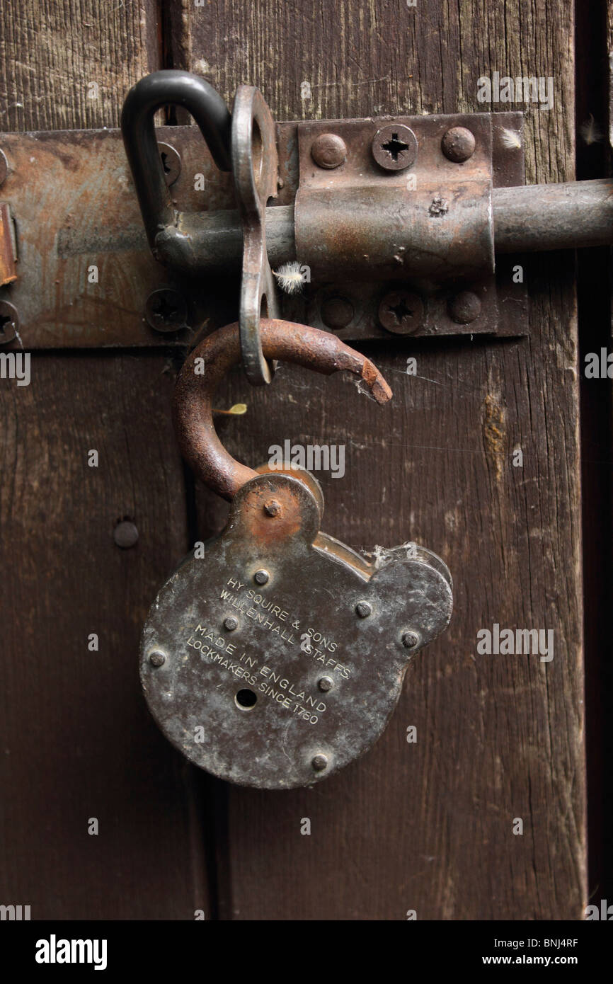 Rusty padlock on rustic wooden door - Stock Image