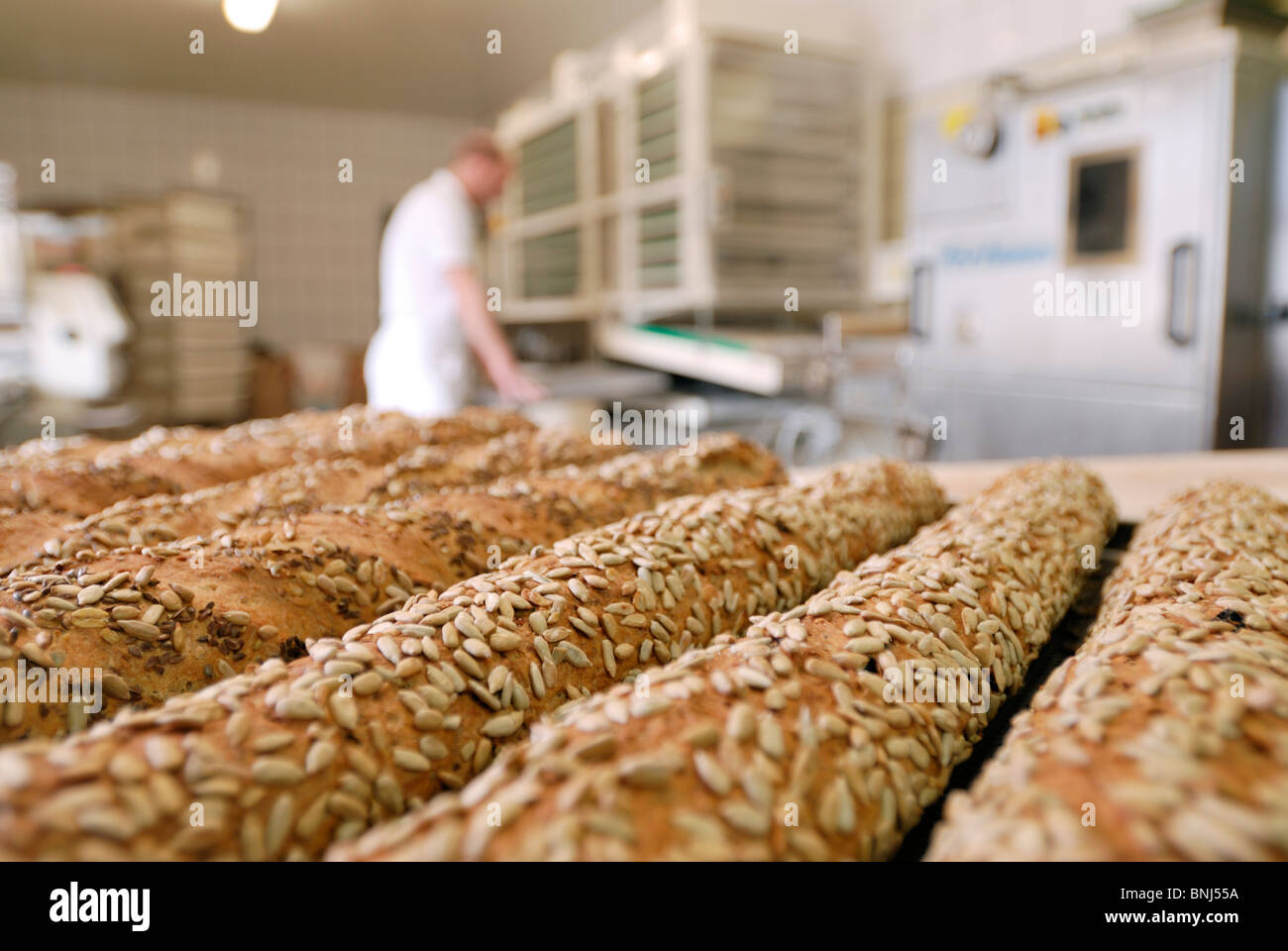 completed bread rolls in front, blurred working baker behind - Stock Image