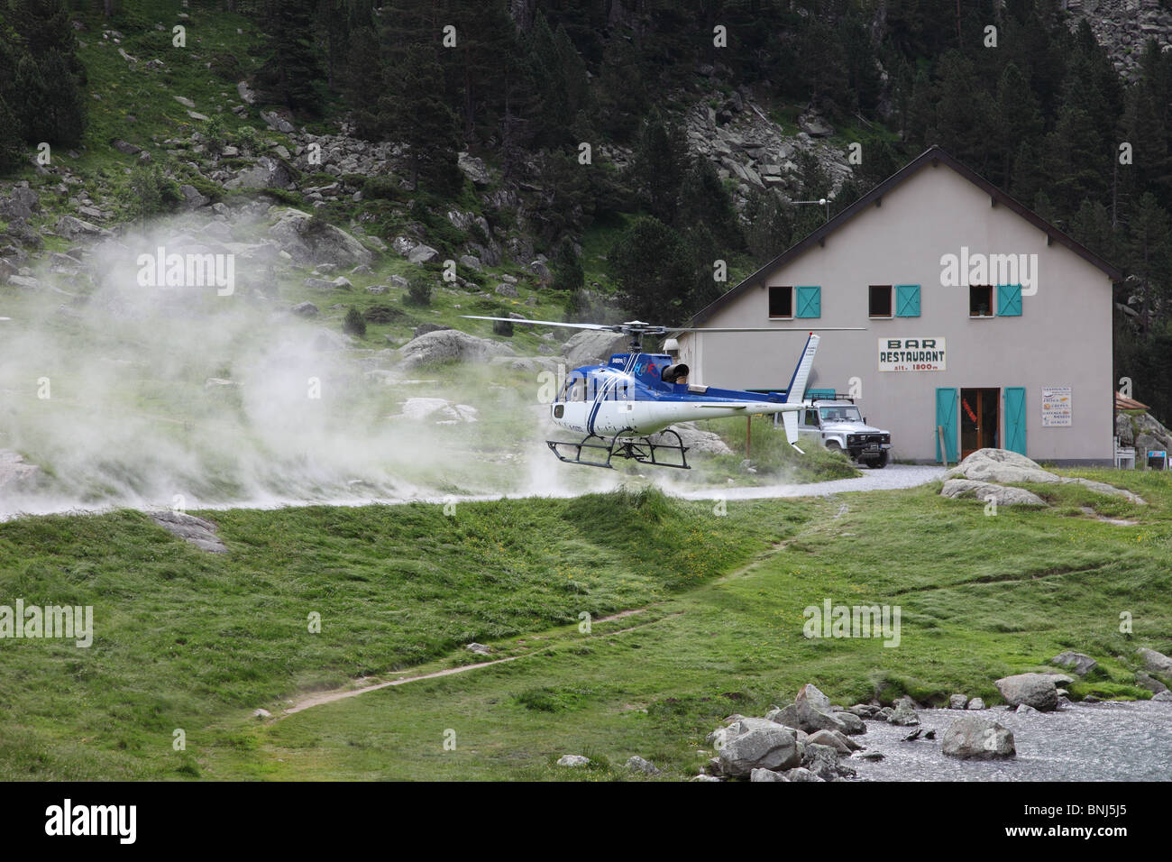 Helicopter Landing Next to a Restaurant at the Lac De Gaube in the French Pyrenees to Collect Supplies - Stock Image