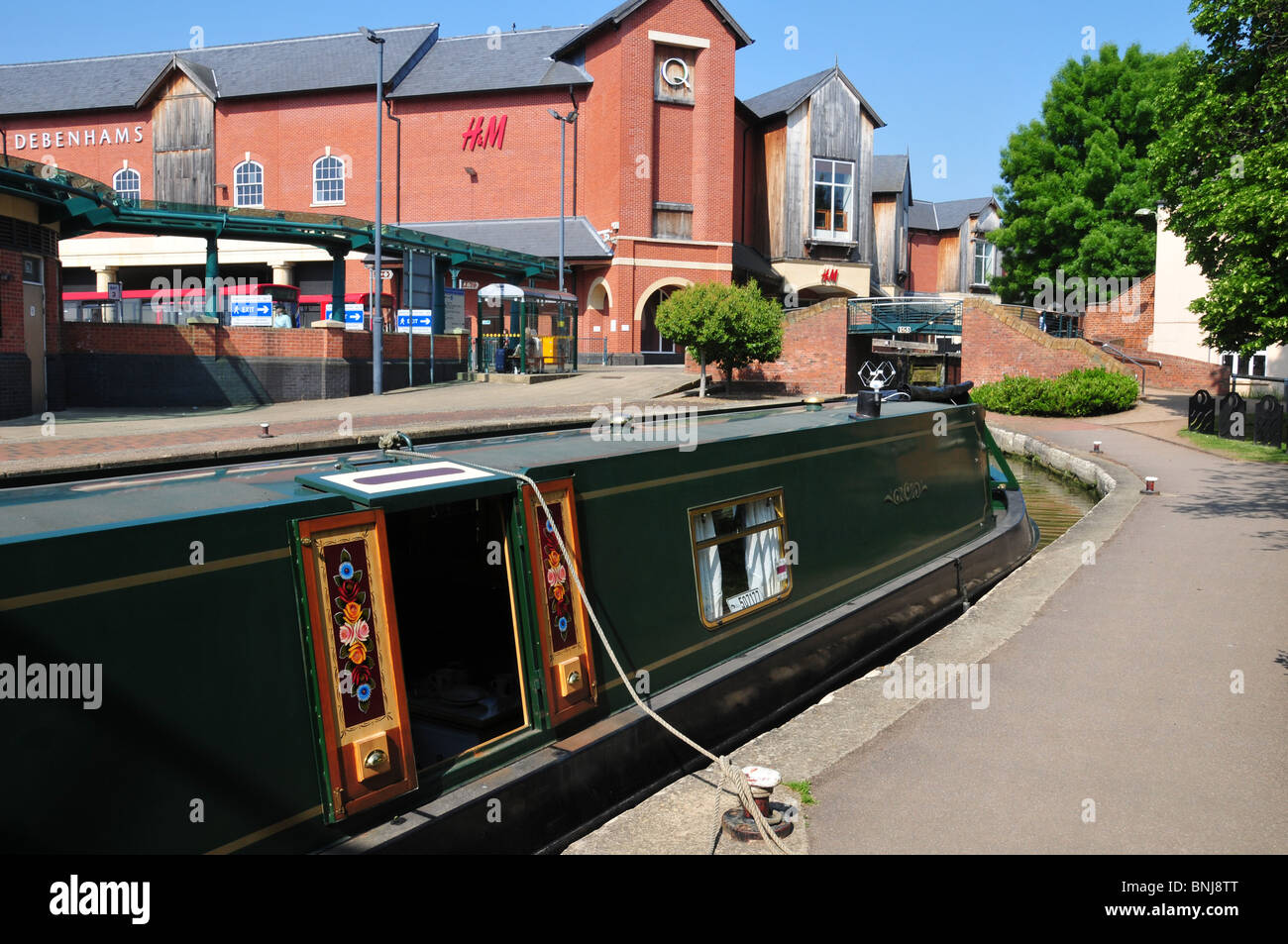 Narrowboat moored on Oxford Canal at Banbury with Castle Quay Shopping Centre to rear - Stock Image
