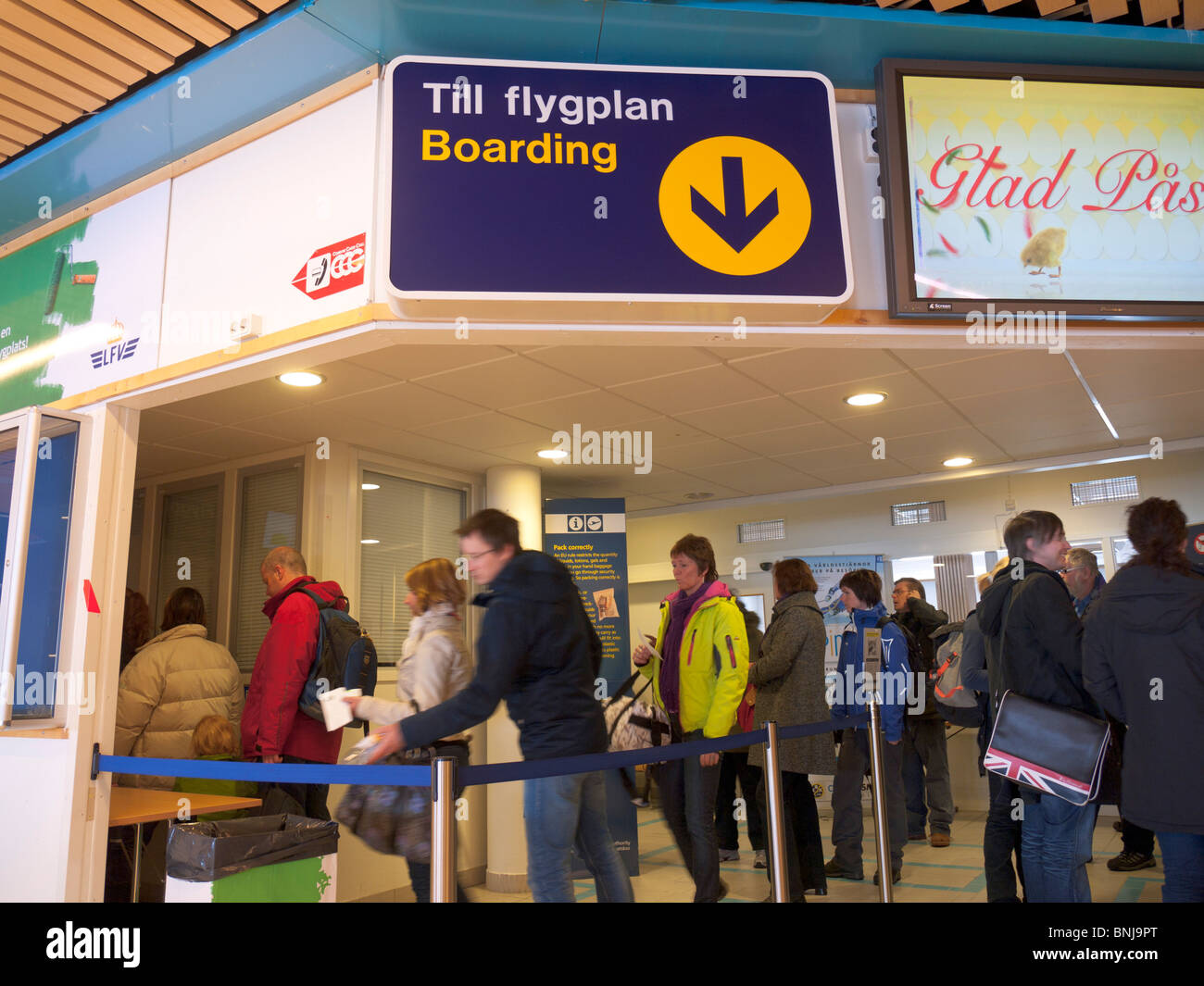 Passengers stand in a queue in the boarding area inside the Kiruna airport. - Stock Image