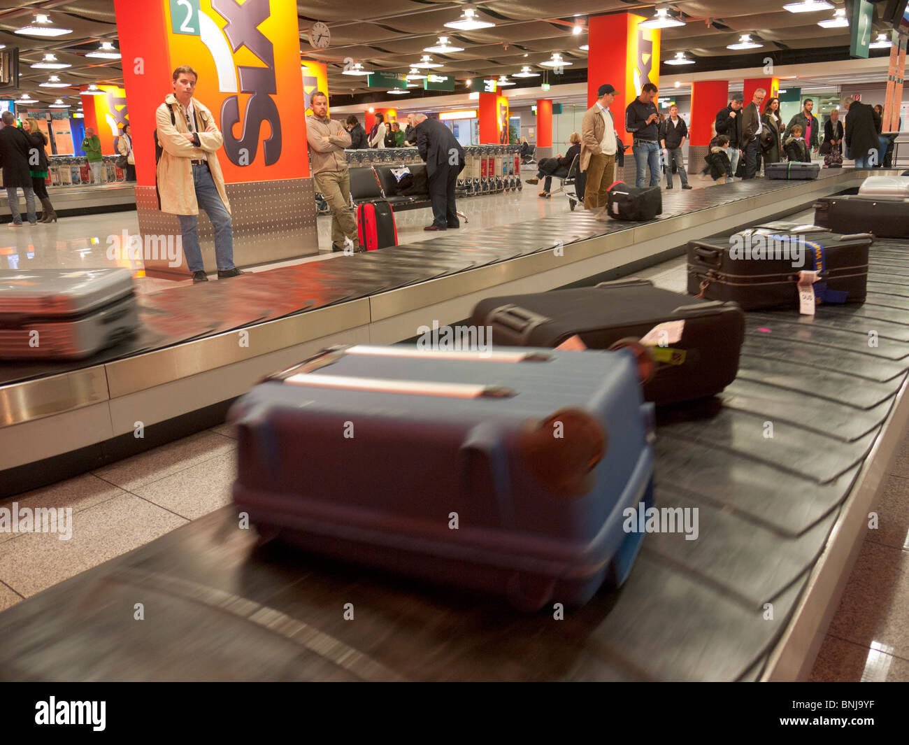 Cases / suitcases / trunks arrive on the conveyor belt at the baggage collection of the Dusseldorf airport. - Stock Image