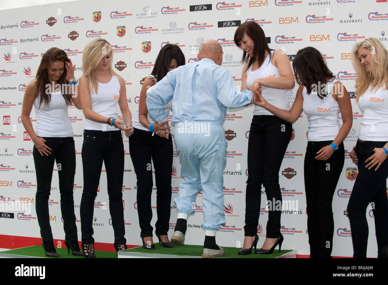 Racing driver Sir Stirling Moss with BSM promotions girls at the Silverstone Classic 2010 motor racing event - Stock Image