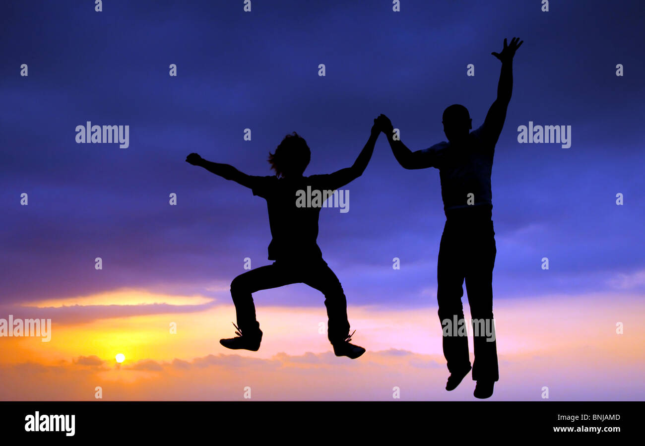 Two happy jumpers over sunset summer sky - Stock Image