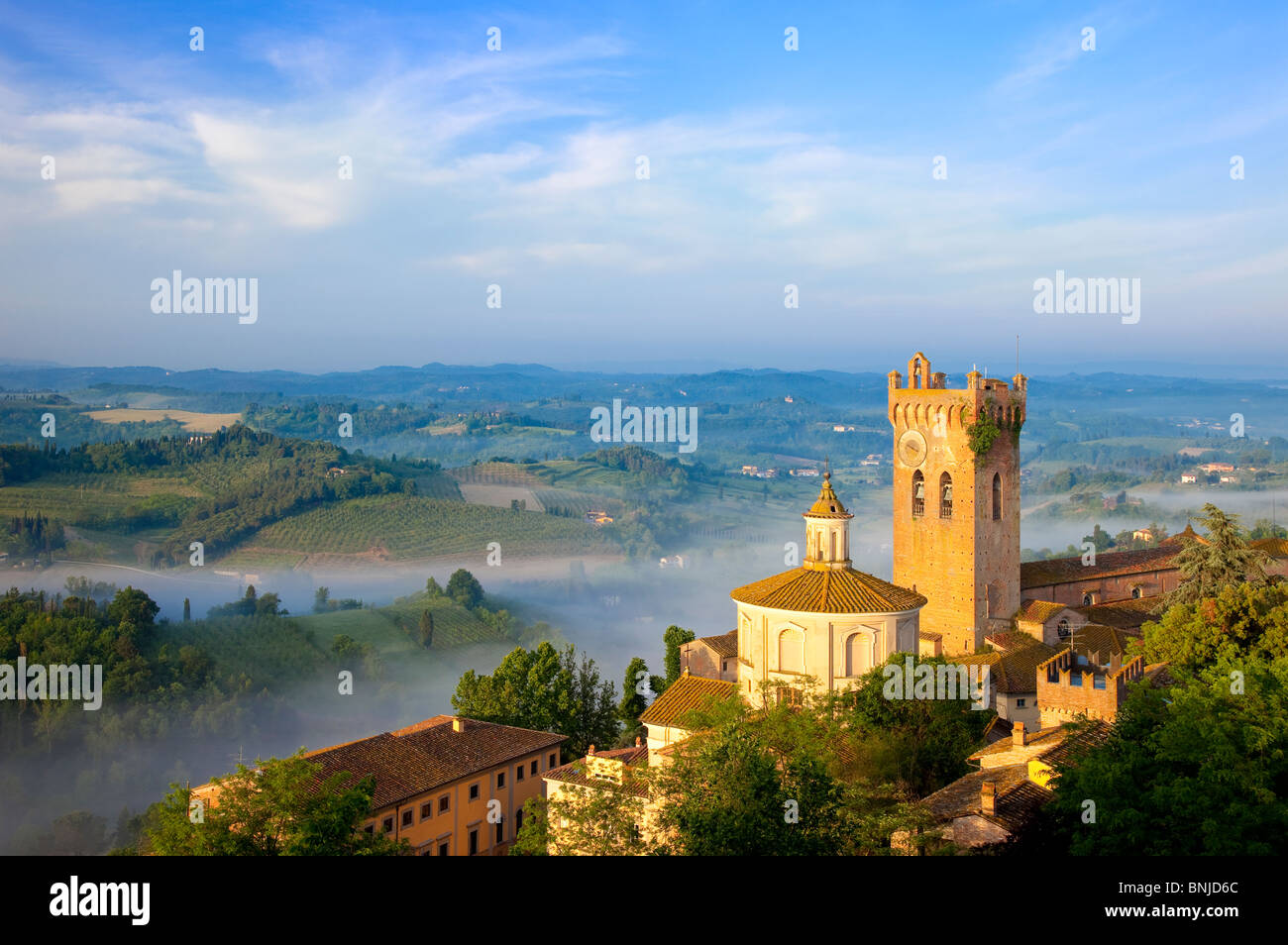 Morning mist laying in the valley below the duomo and medieval town of San Miniato, Tuscany Italy Stock Photo