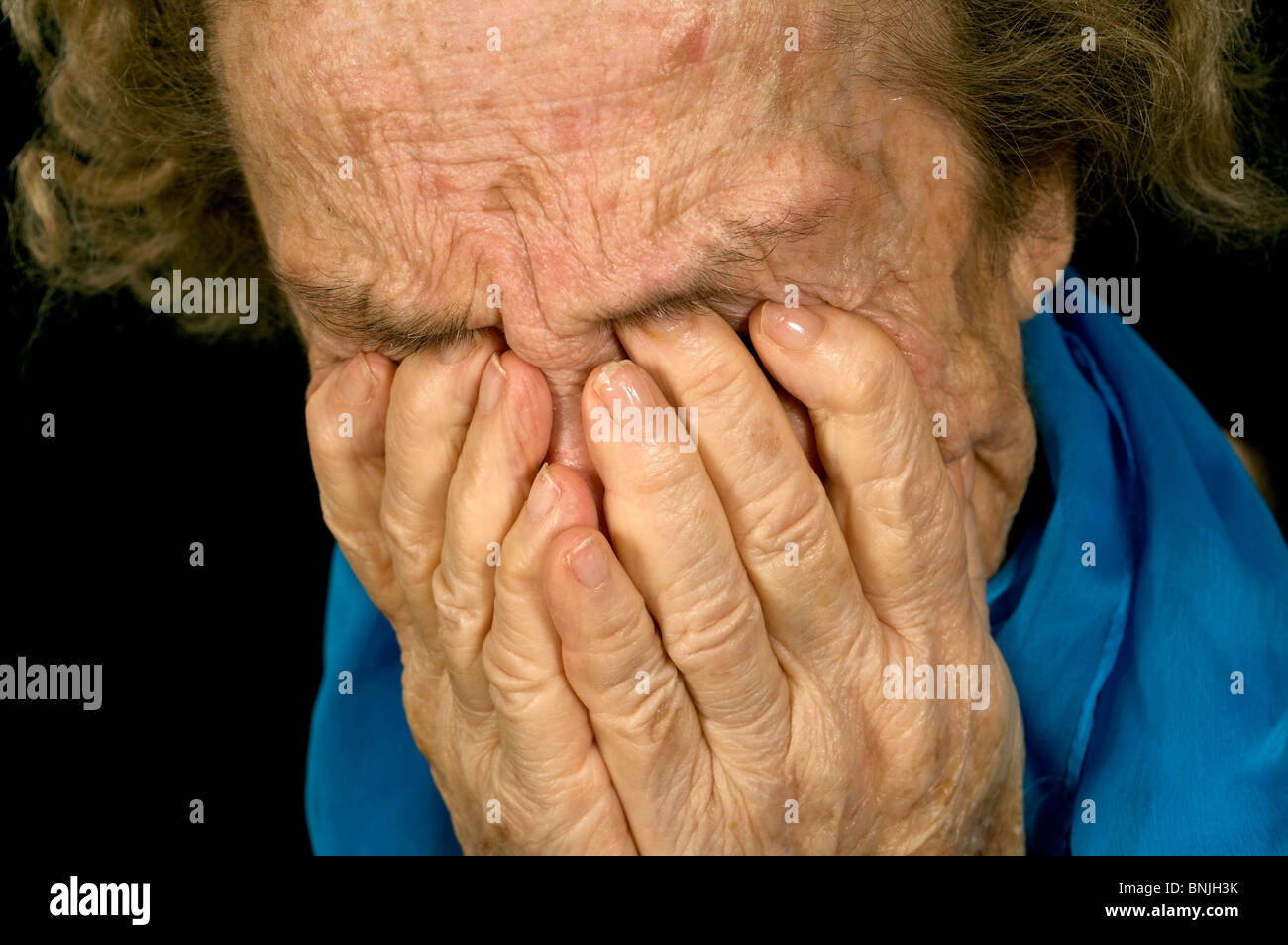 Sad Old Women with her hands to her face is dismay - Stock Image