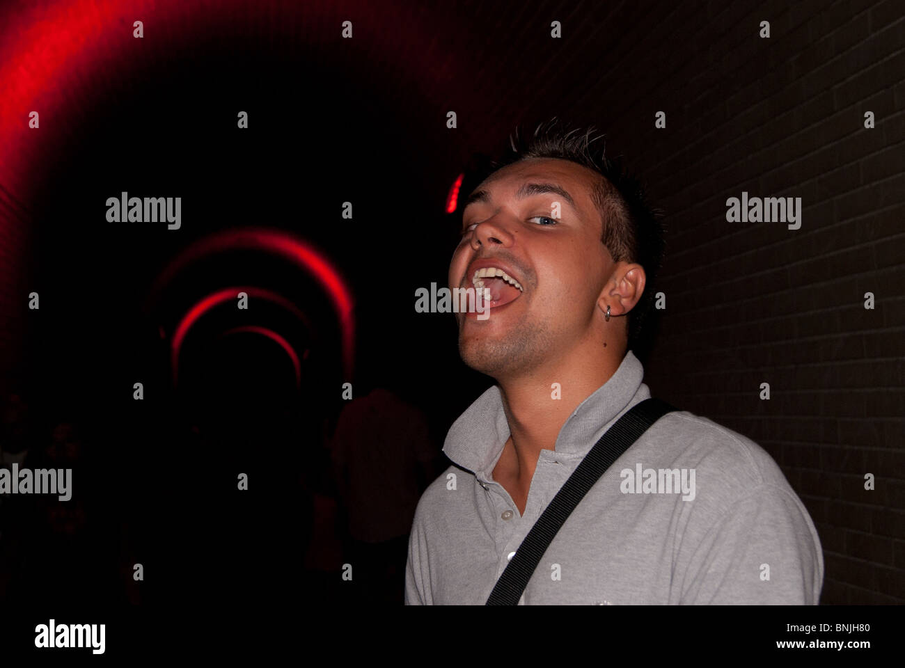 The guy sings in the tunnel, tunnel is dark with the crimson neon light - Stock Image
