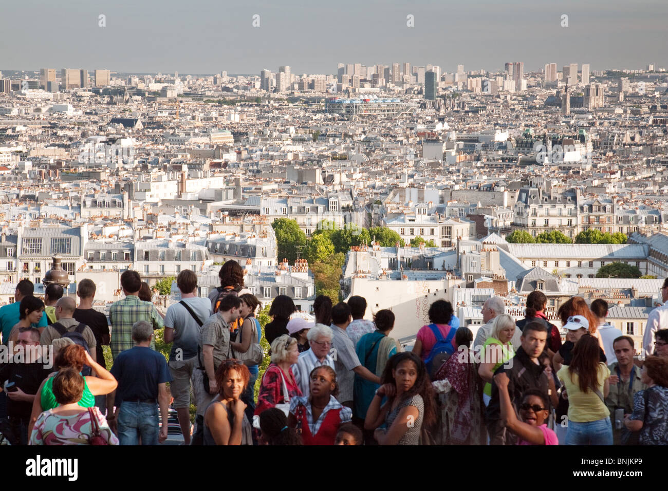 Crowds of  tourists look out at the view over Paris from the Basilique du Sacre Coeur, Montmartre, Paris, France - Stock Image