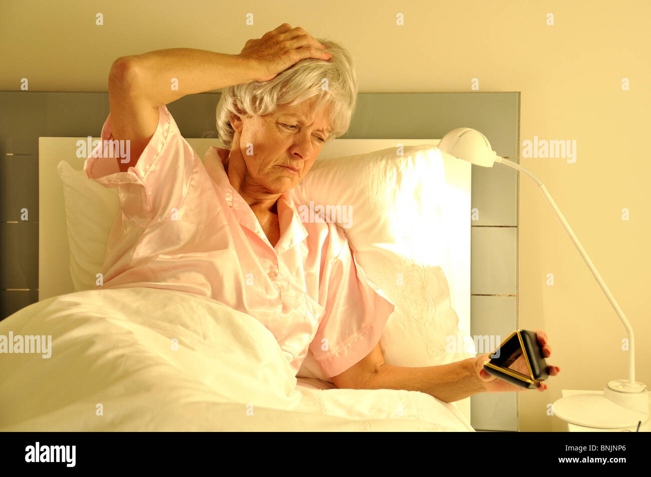 Midnight Unwell Sleepless Early Tired Alarmclock clock awake weak Bedroom Old Senior mature Bed Pensioner Woman - Stock Image