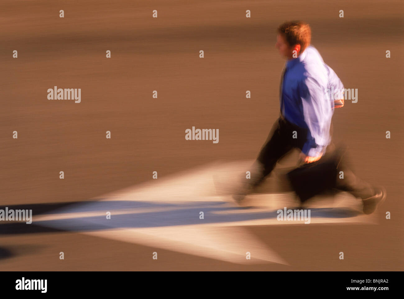 Businessman with briefcase hurrying to work over street direction arrow - Stock Image