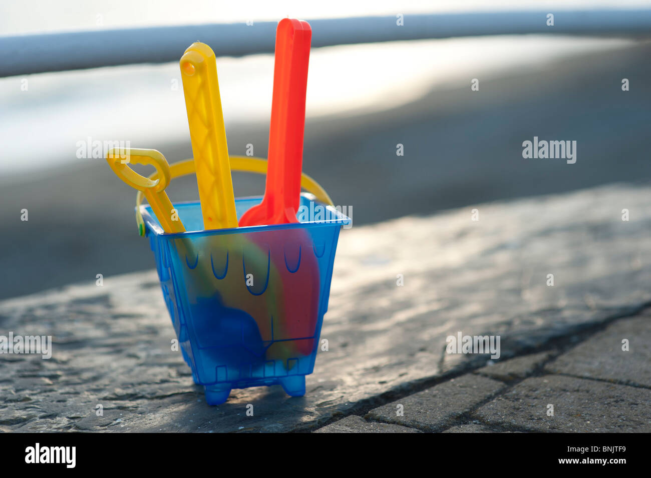 Plastic bucket and spade at the seaside - Stock Image