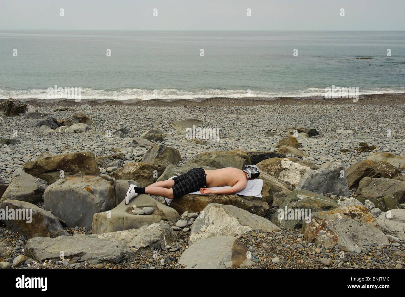 A man sunbathing on the beach lying face down on rocks , Aberystwyth Wales UK - Stock Image