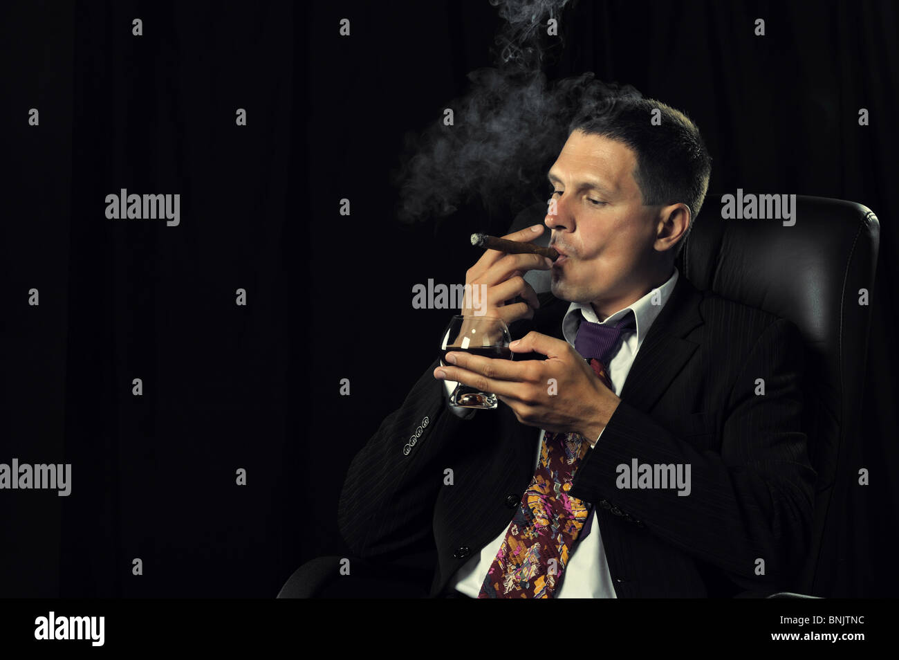 The man with a cigar and a glass of cognac. A dark background - Stock Image