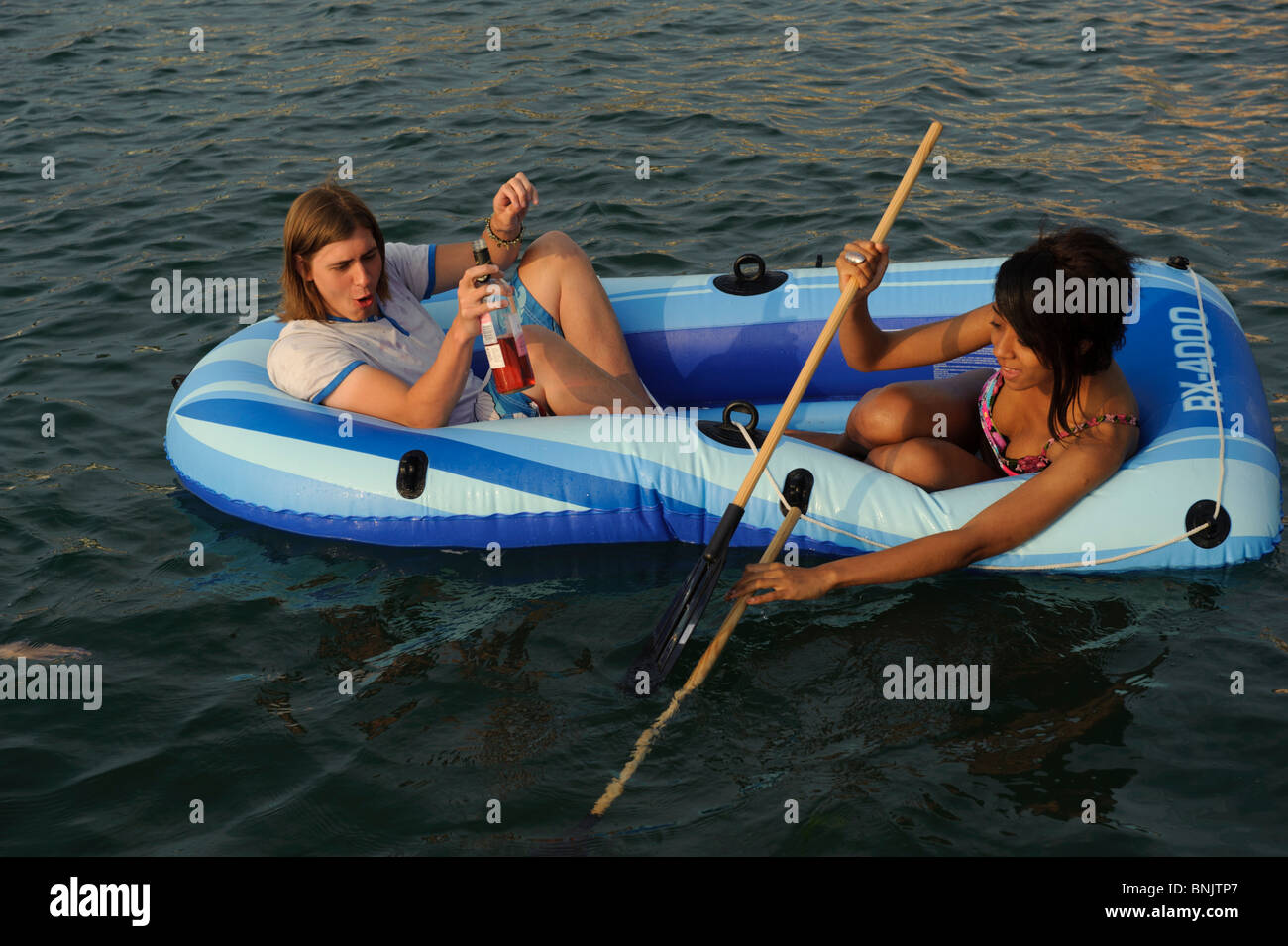 Two Young people in an inflatable dinghy drinking a bottle of wine, Aberystwyth Wales UK - Stock Image