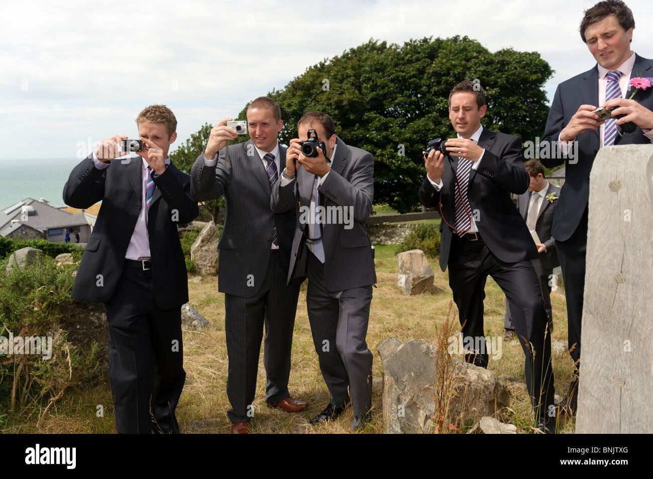 Five men wearing suits guests at wedding taking photographs on their digital cameras, UK - Stock Image