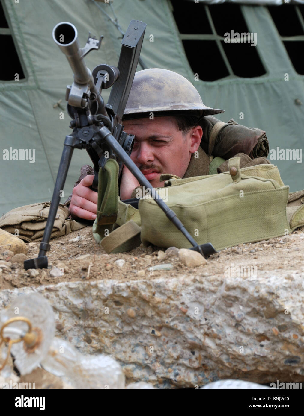 A re-enactor in the role of a second world war British soldier defending a position with a Bren machine gun. - Stock Image