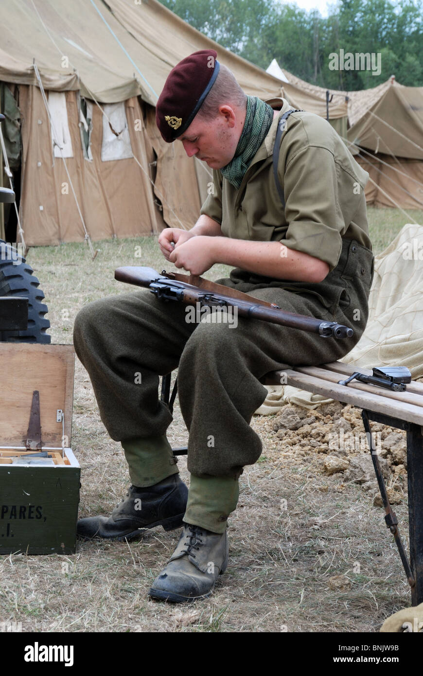 A re-enactor depicts a World War 2 British soldier cleaning his Lee Enfield rifle - Stock Image