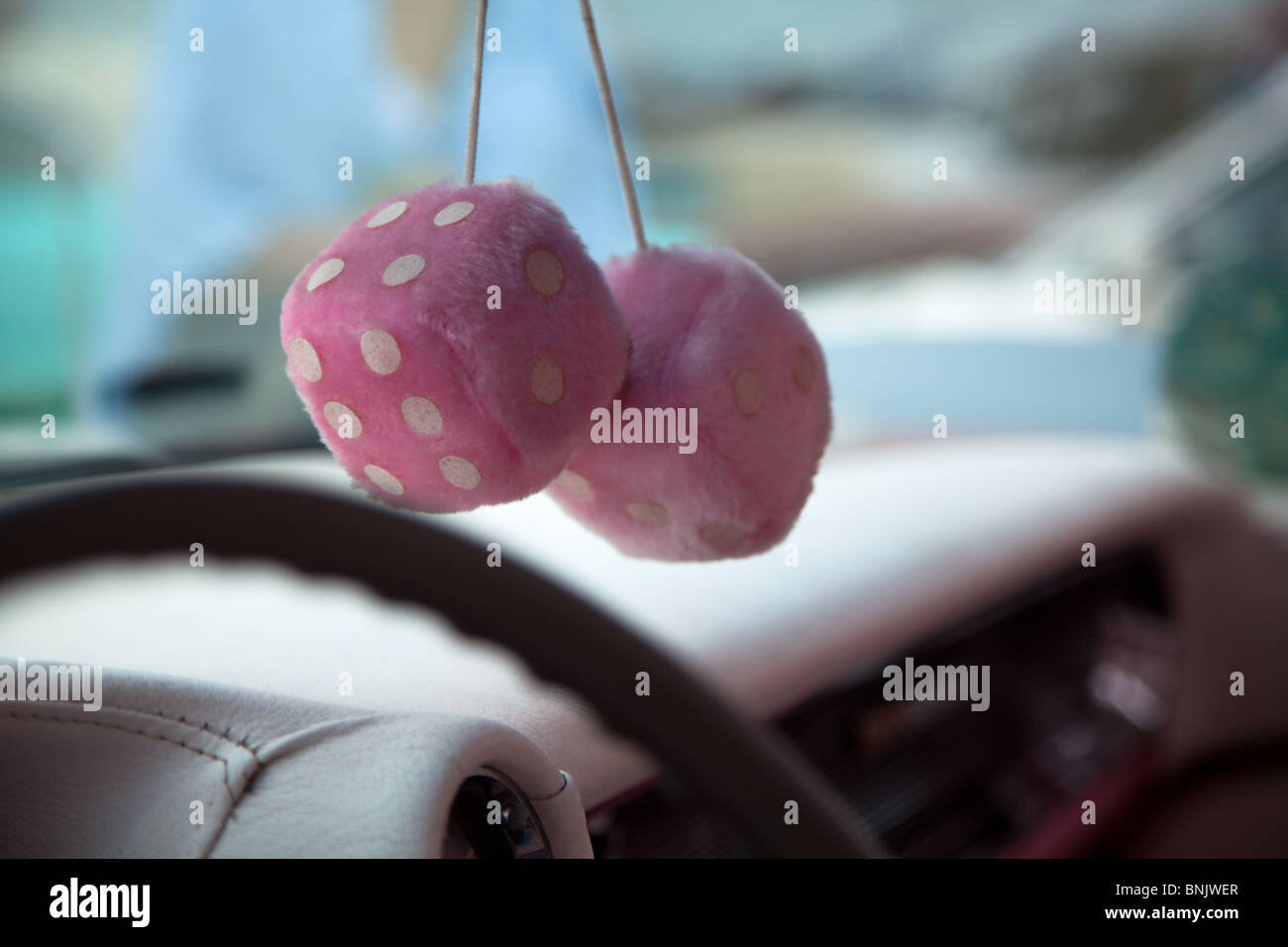A close up shot of a pair of Pink fluffy furry dice hanging from the rear view mirror in an old car at Fairford, - Stock Image