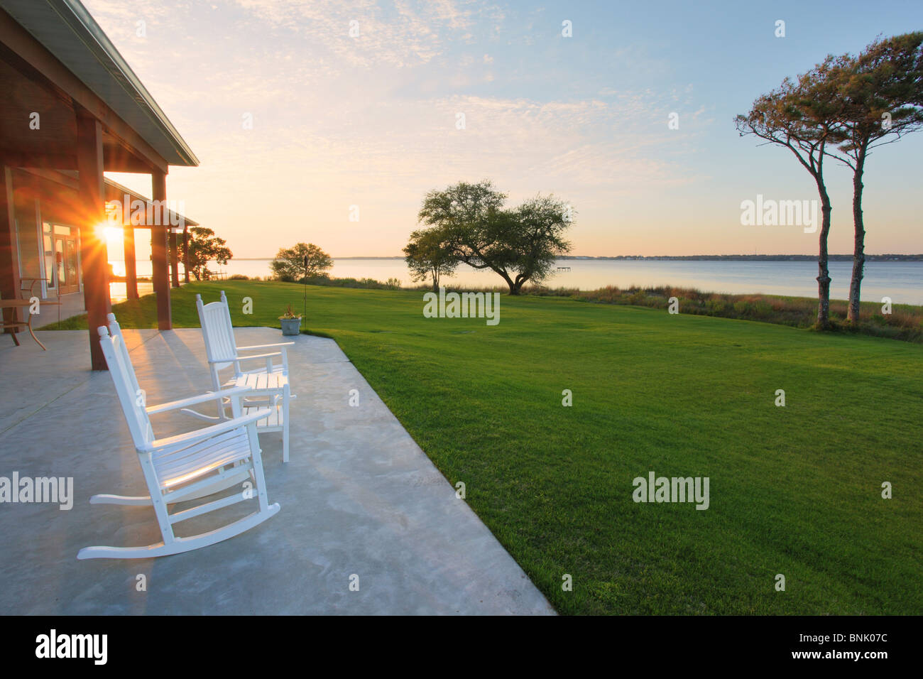Rocking chairs on patio overlooking sunset over Bogue Sound, Country Club of Crystal Coast, Atlantic Beach, North - Stock Image
