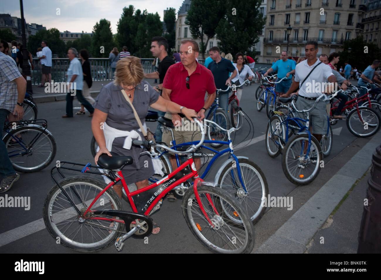 Paris Bicycle Tour, Adult Tourists Cycling on Pont Saint Louis Bridge, Ile Saint Louis - Stock Image