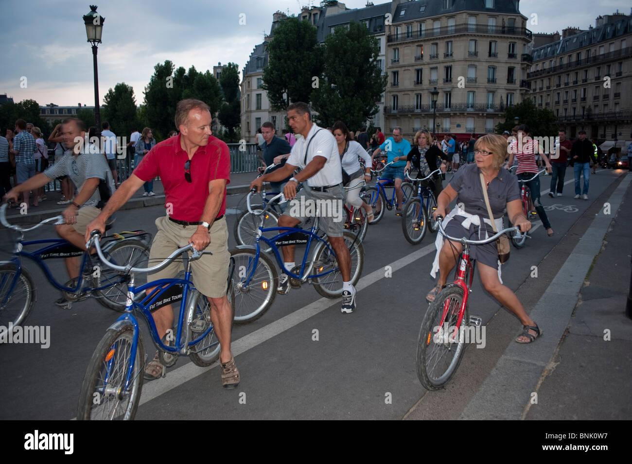 Paris Bicycle Tour, Group Adult Tourists Visiting on 'Pont Saint Louis' Bridge, (Ile Saint Louis) Street - Stock Image