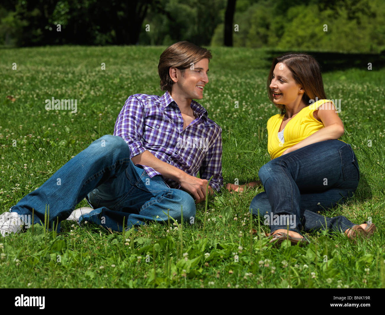 Young happy couple in their early thirties lying on grass in a park - Stock Image