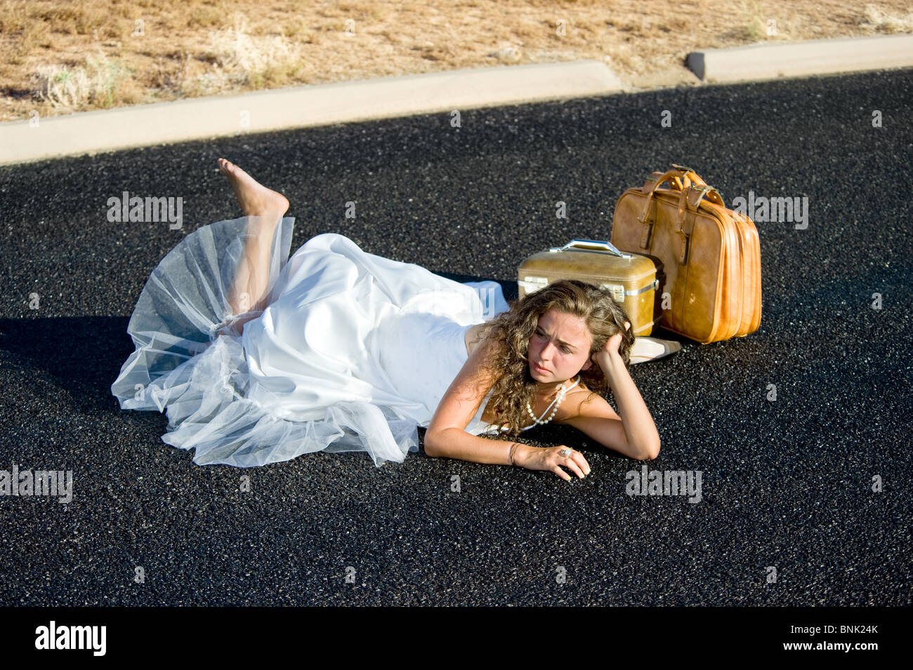 A bride is kicked to the curb and all alone along an isolated street. - Stock Image