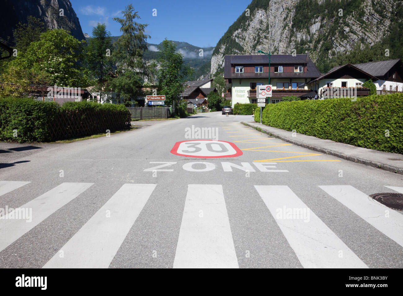 Austria, Europe. Pedestrian crossing and thirty kilometers an hour speed restriction zone sign on road - Stock Image