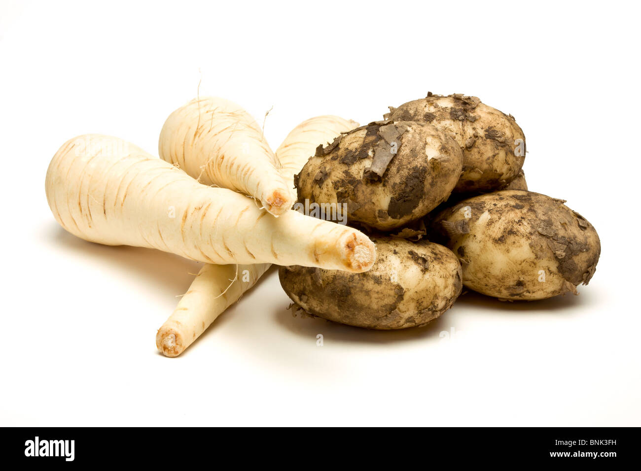 Root vegetables of Parsnip and New Potatoes from low perspective isolated against white background. - Stock Image