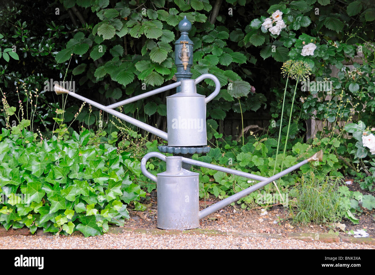 Two galvanised watering cans under ornate tap, garden, London. - Stock Image