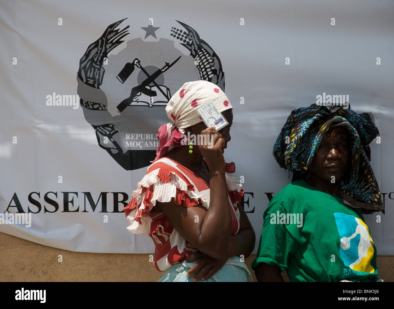 Women brandishing their id cards wait in line for their chance to vote in Mozambique's general election in November - Stock Image