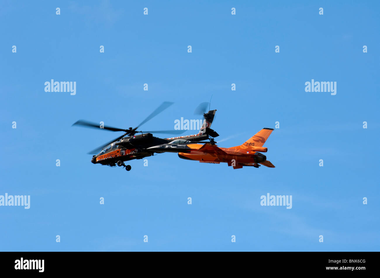 Royal Netherlands Airforce Boeing AH-64D Apache and General Dynamics F16-AM Fighting Falcon fly together - Stock Image