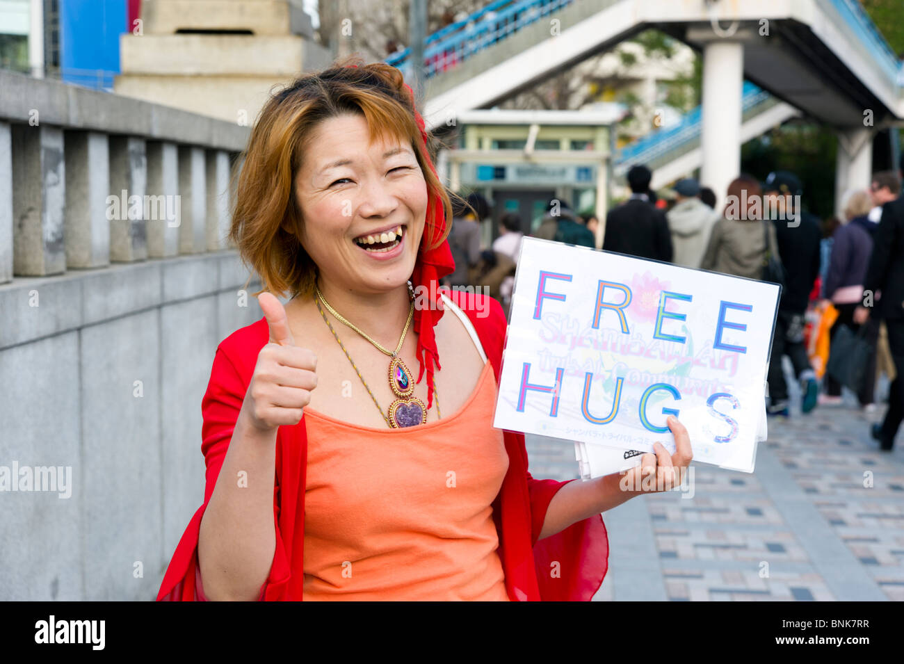 Young woman offering free hugs to raise awareness of youth suicide, Harajuku, Tokyo, Japan - Stock Image