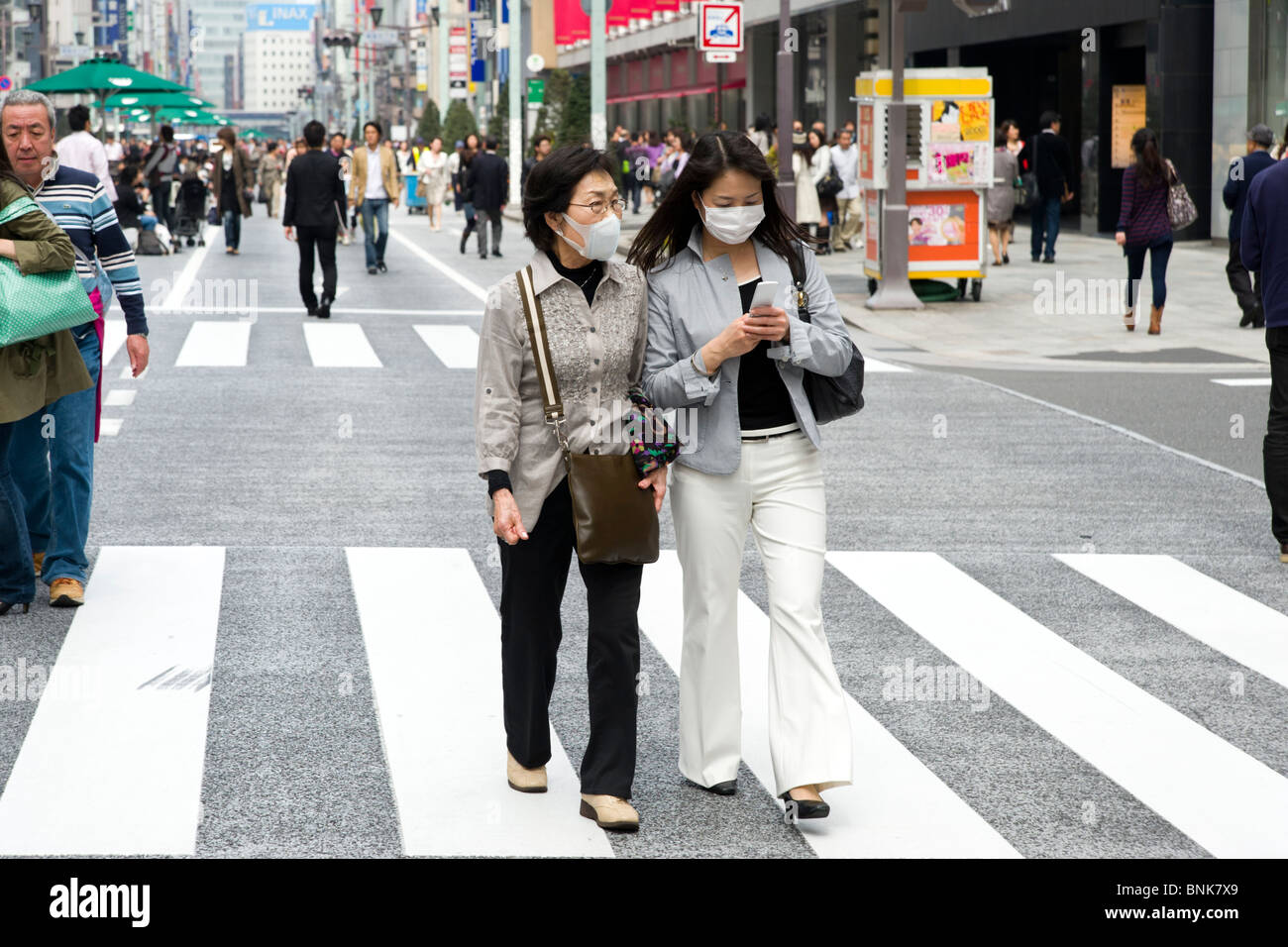 Women wearing protective face masks in Chuo-dori in Ginza 4-chome, Tokyo, Japan - Stock Image