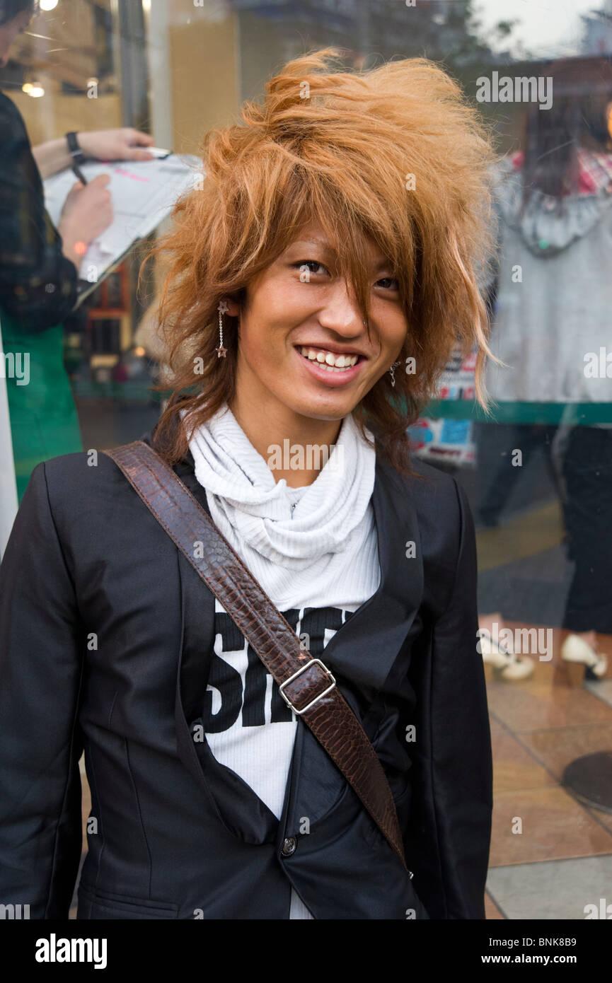 Trendy teenager with dyed orange hair in Shibuya, Tokyo, Japan - Stock Image