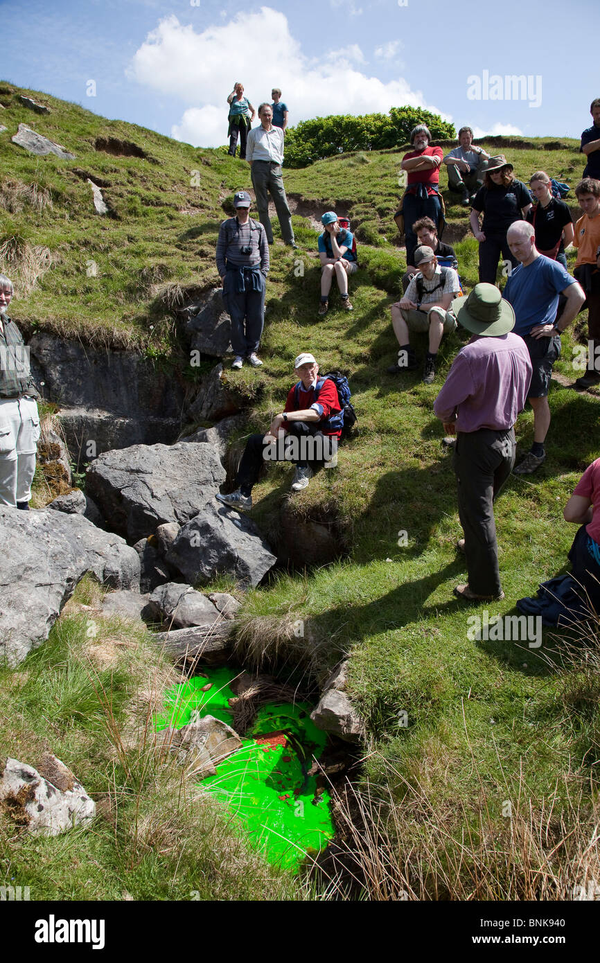 Man talking to science group about hydrology and dye tracing using fluorescein in stream sink Derbyshire UK - Stock Image