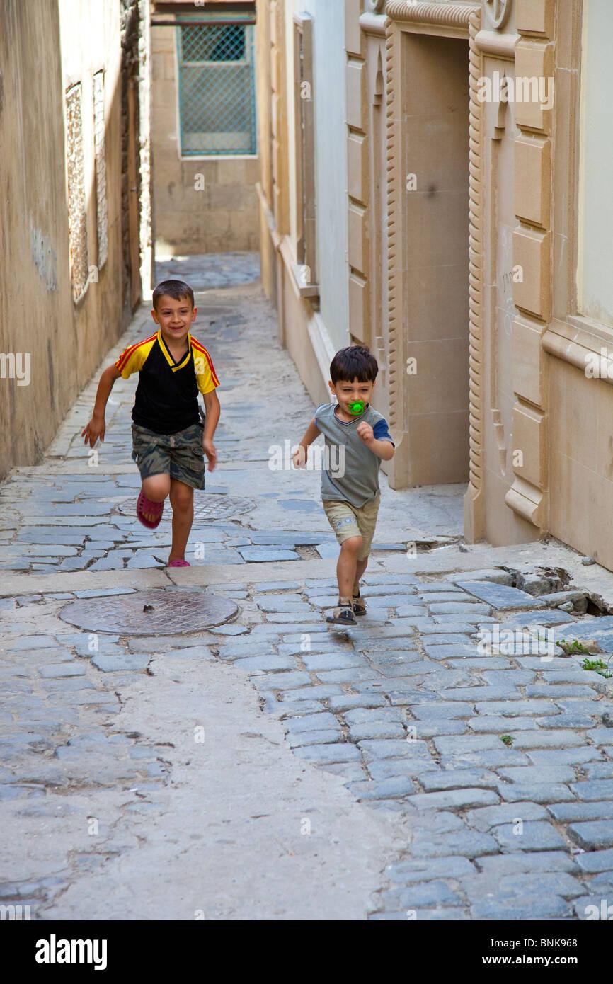 Boys inside the old city in Baku, Azerbaijan - Stock Image
