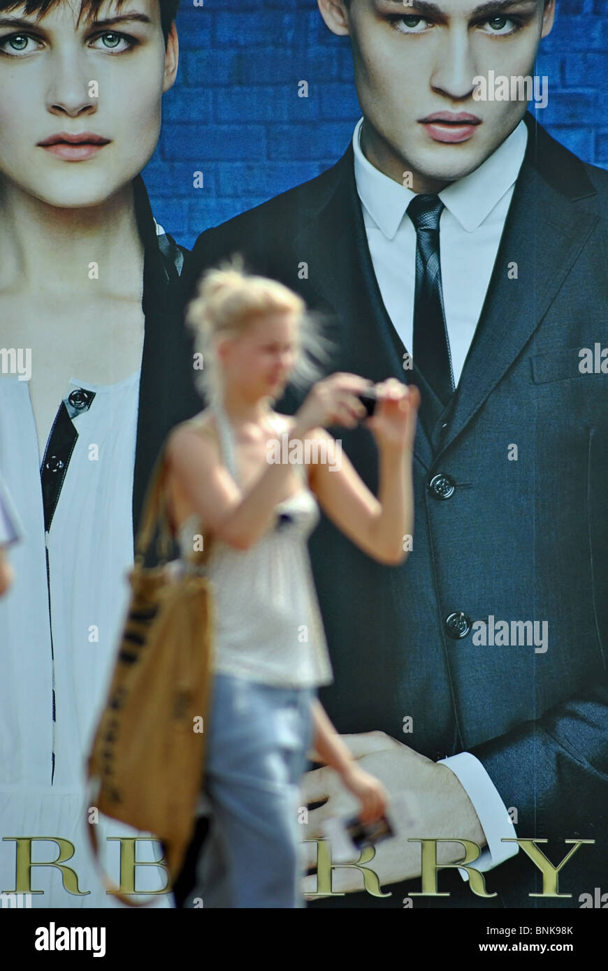 People walk past billboards advertising Burberry clothes, Venice, Italy - Stock Image