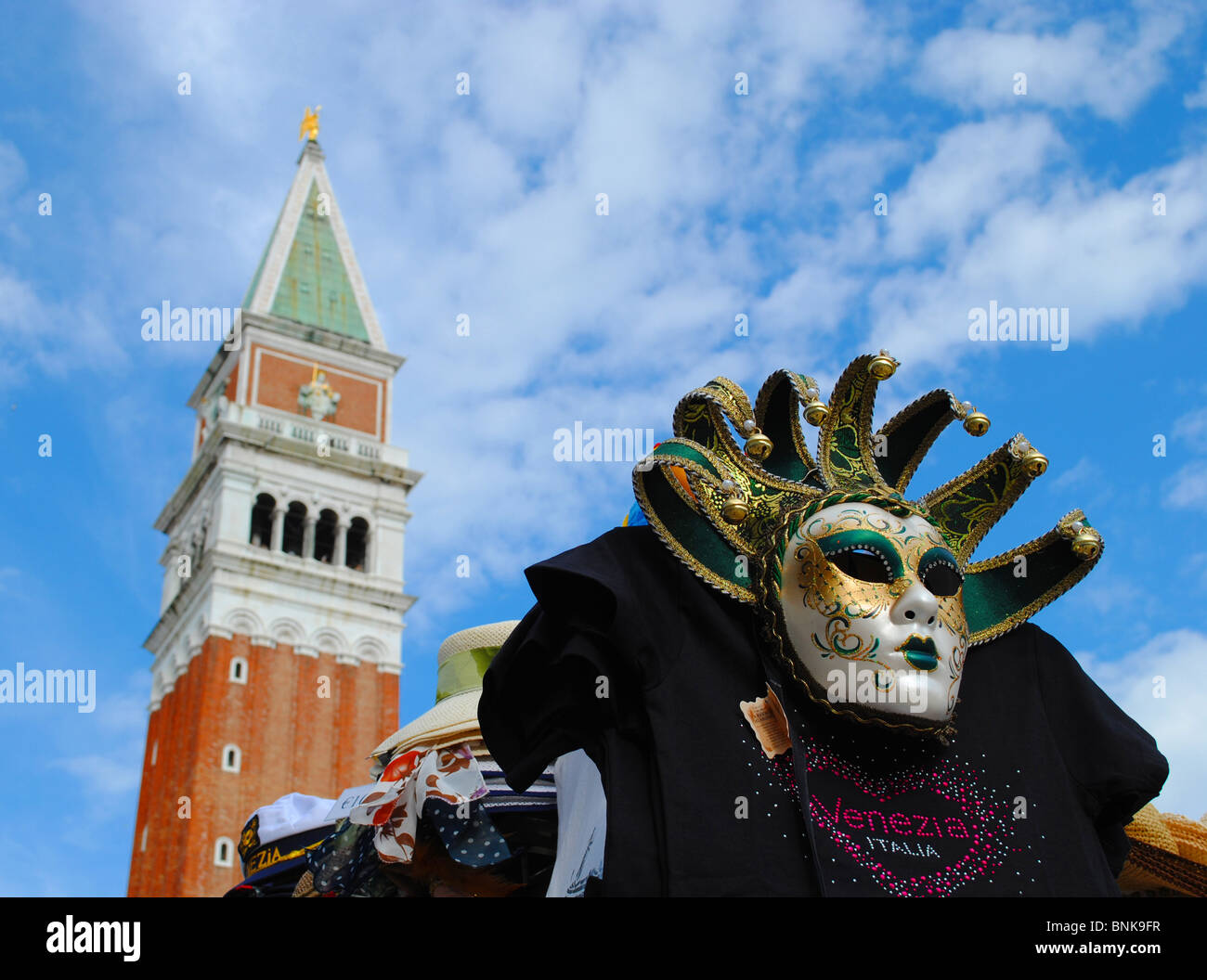 Mask and Bell tower in St Mark's square, Venice, Italy - Stock Image