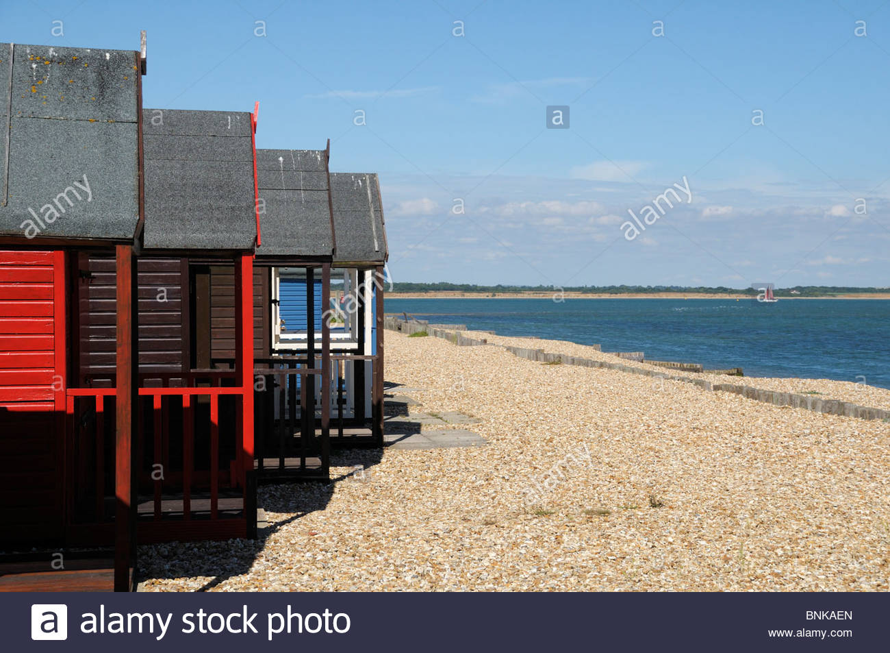 Picturesque image of staggered beach huts on the seafront at Calshot in Hampshire, England - Stock Image