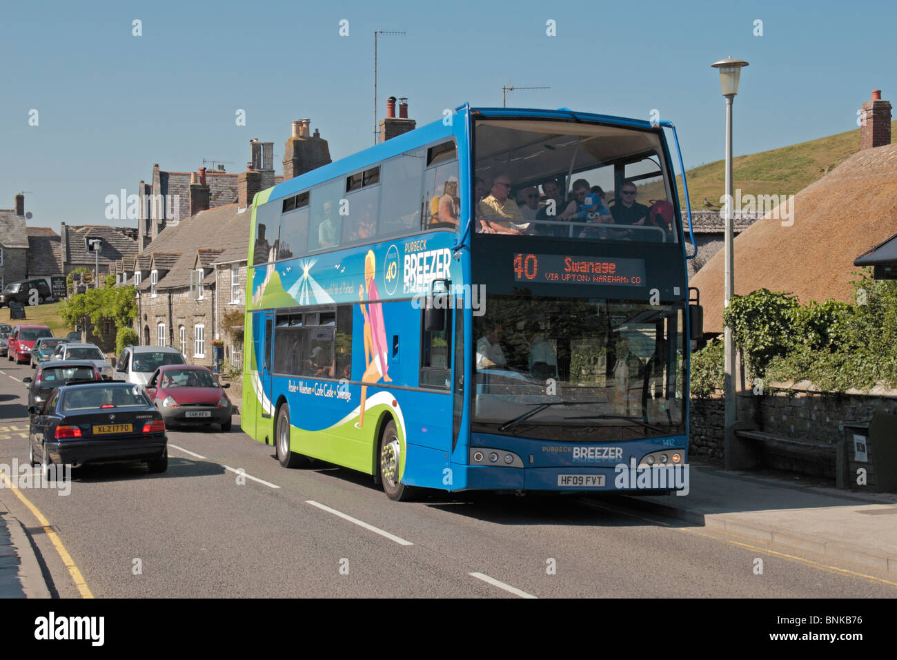 A local Purbeck Breezer public bus, Route 40, on its way to Swanage, blocking traffic in Corfe Castle, Dorset, UK. - Stock Image