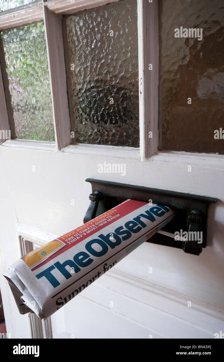 A copy of the English newspaper, The Observer, delivered to a house and sticking out of the letterbox - Stock Image