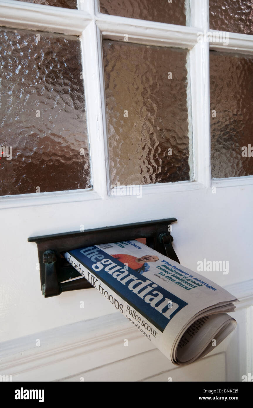 A copy of the English newspaper, The Guardian, delivered to a house and sticking out of the letterbox - Stock Image