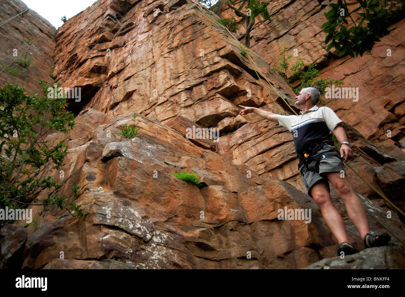 Middle aged Caucasian male at the base of a cliff. Monteseel Conservancy, Inchanga, Kwa-zulu Natal South Africa - Stock Image